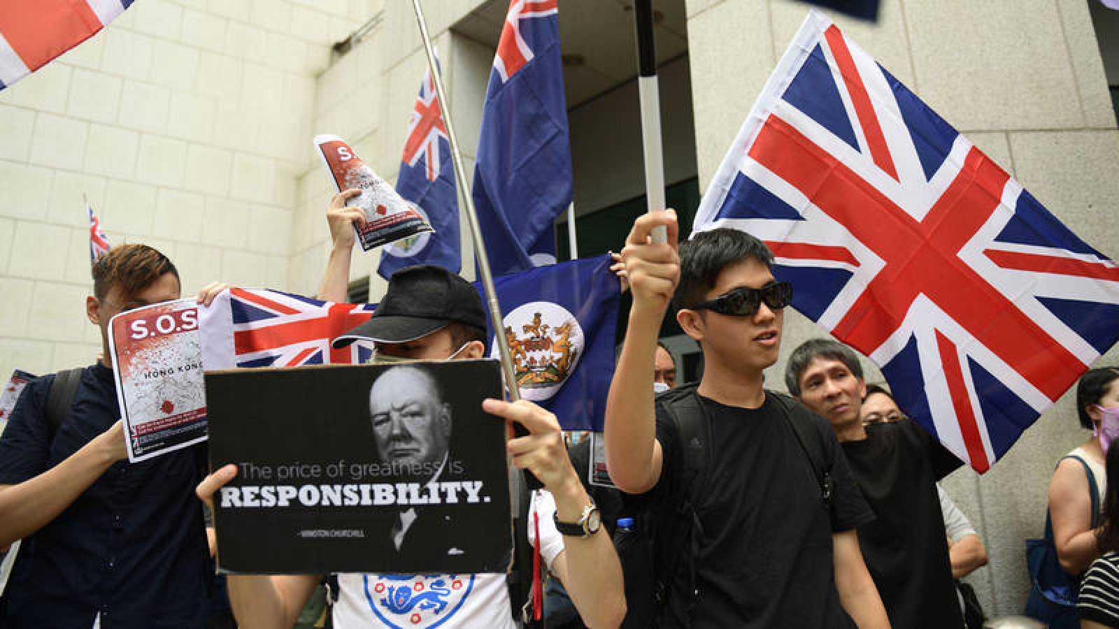 """Un manifestante sostiene una pancartacon la imagen deChurchill y su famosa cita: """"El precio de la grandeza es la responsabilidad""""."""