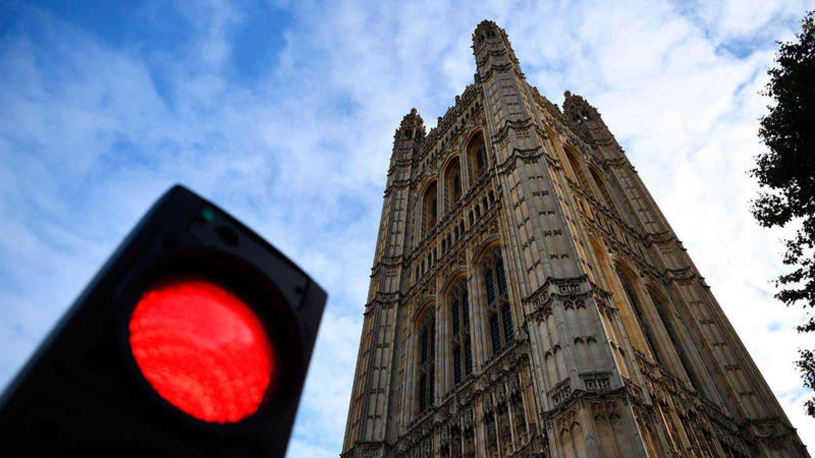 Semáforo rojo delante de la torre del parlamento británico.