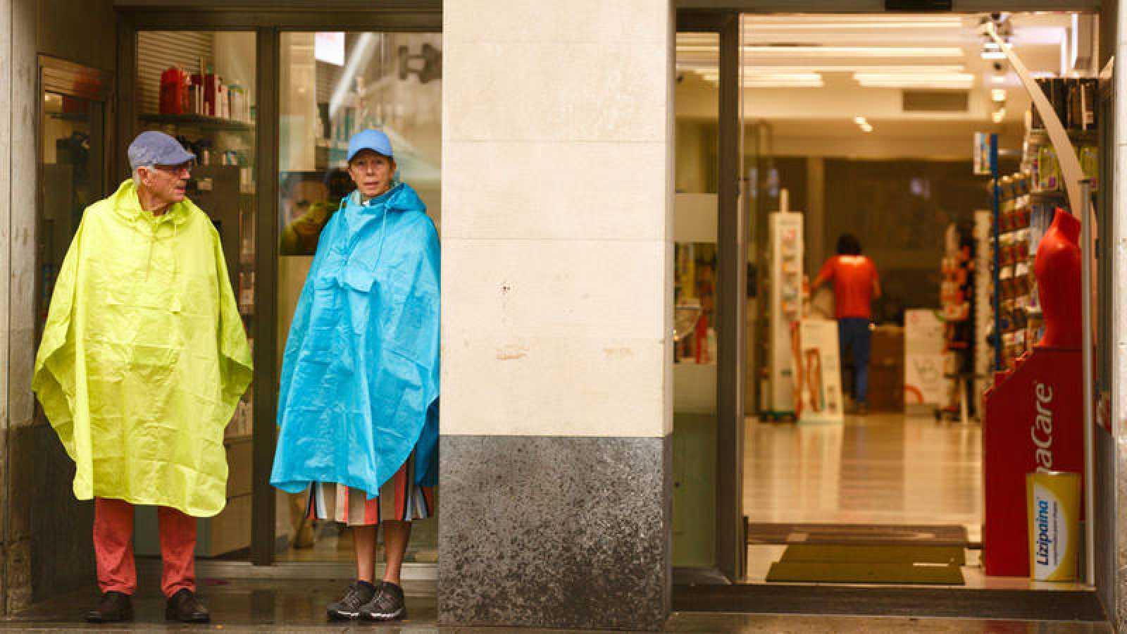 Dos turistas se protegen de la lluvia en Vitoria
