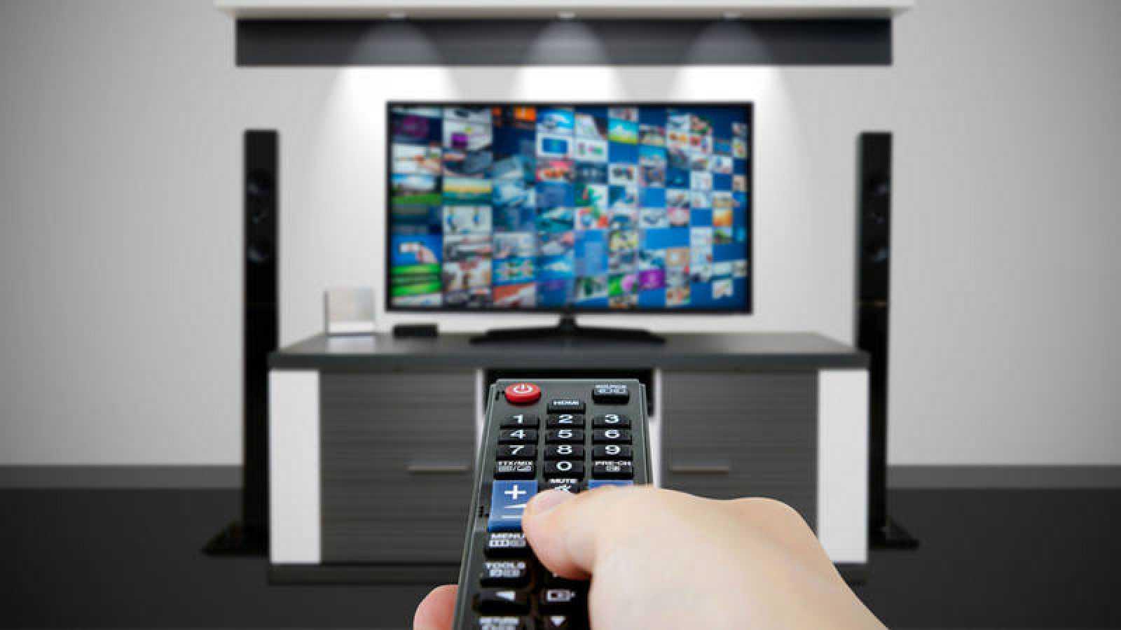 Un televidente resintoniza los canales con el mando a distancia