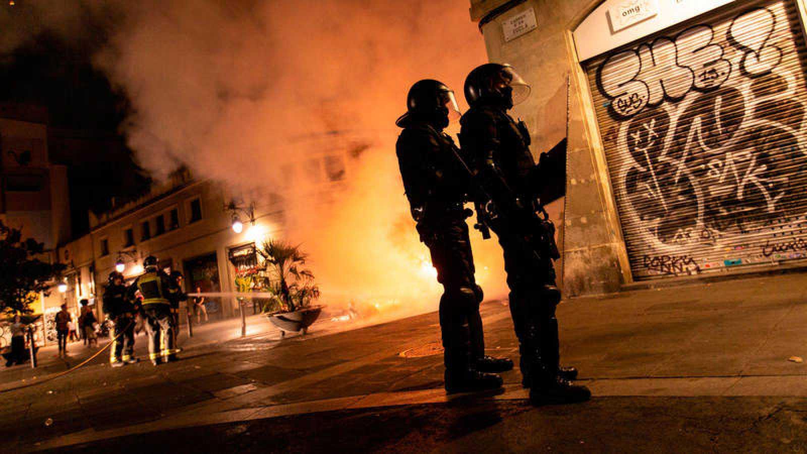 Mossos d'Esquadra controlan una calle de El Raval mientras los bomberos apagan una barricada de fuego