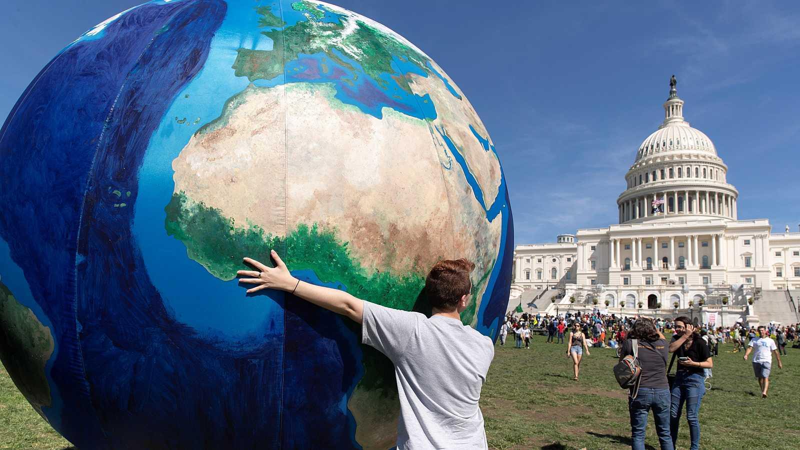 Un joven sostiene un globo terráqueo gigante frente al Capitolio de EE.UU. para protestar contra el cambio climático.