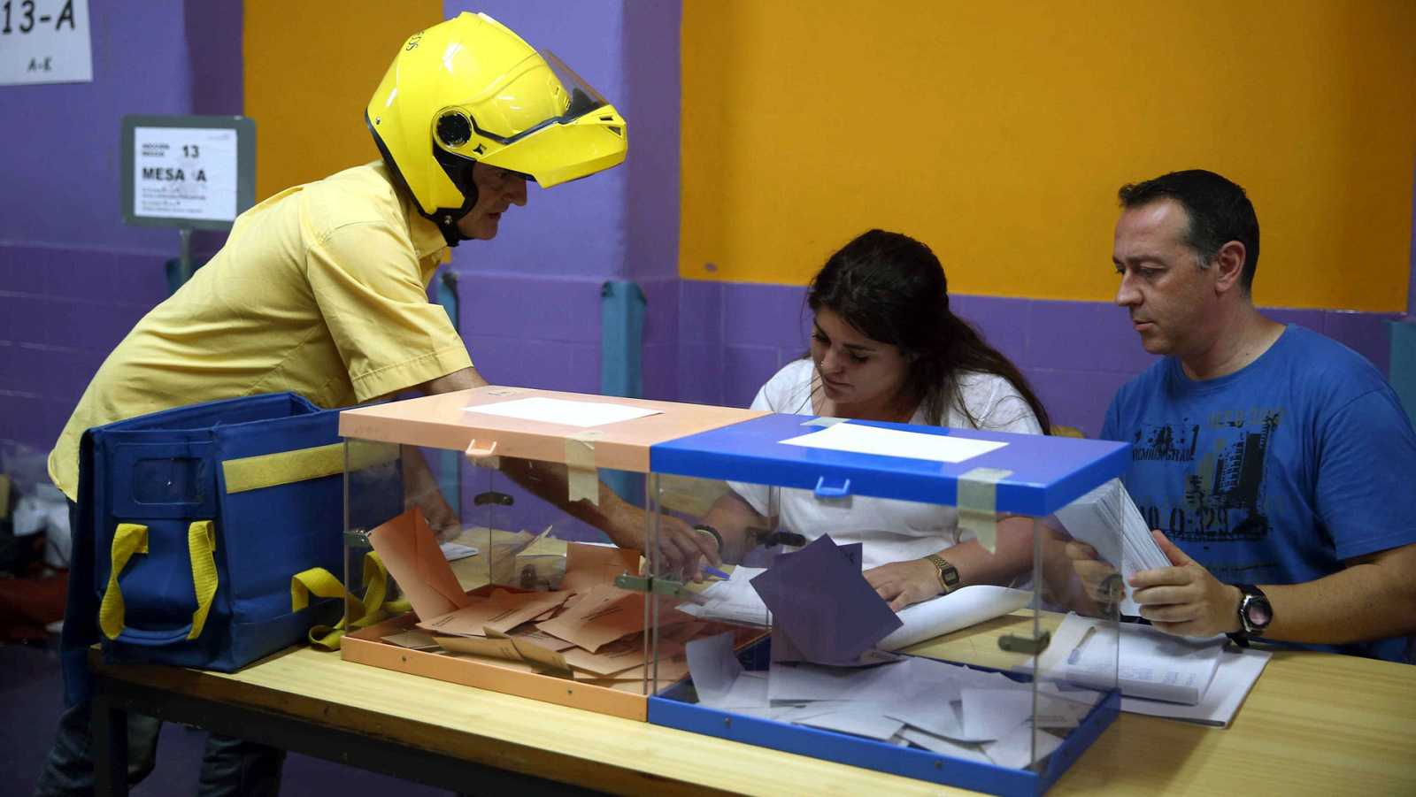 Un cartero entrega el voto por correo en una de las mesas electorales de un colegio de l'Hospitalet de Llobregat.