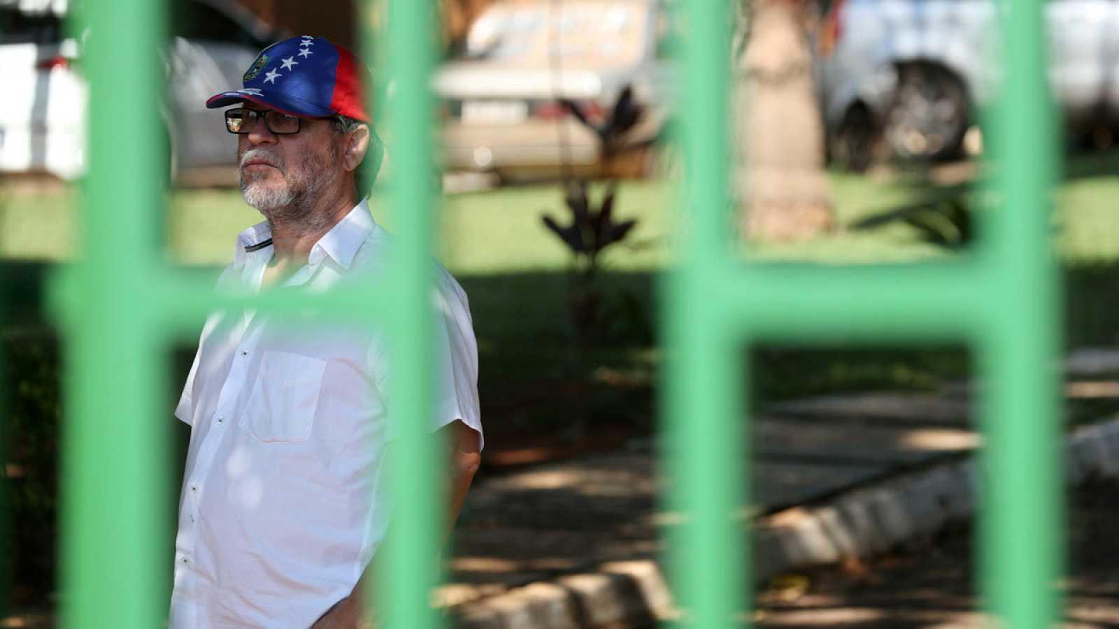Un hombre luce una gorra con la bandera de Venezuela en el recinto de la embajada.