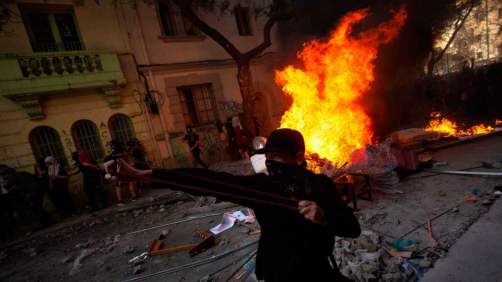 Varios manifestantes encapuchados se enfrentan a las fuerzas de seguridad en una barricada en Santiago de Chile