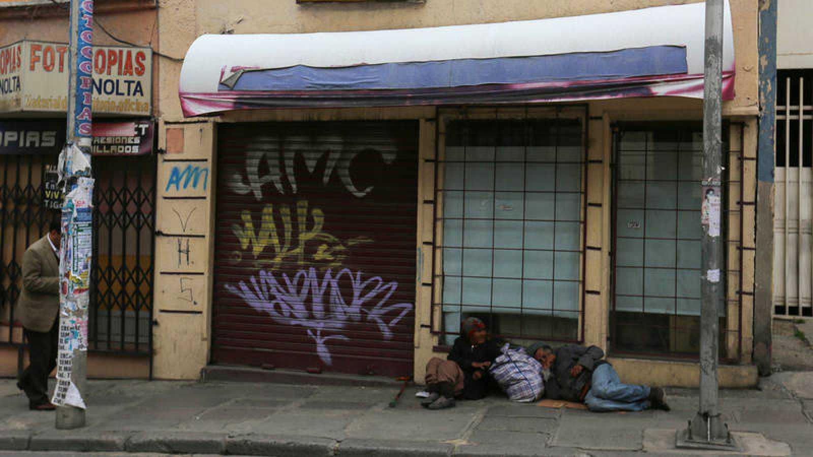 Dos personas duermen en la acera, frente a comercios cerrados en La Paz, Bolivia