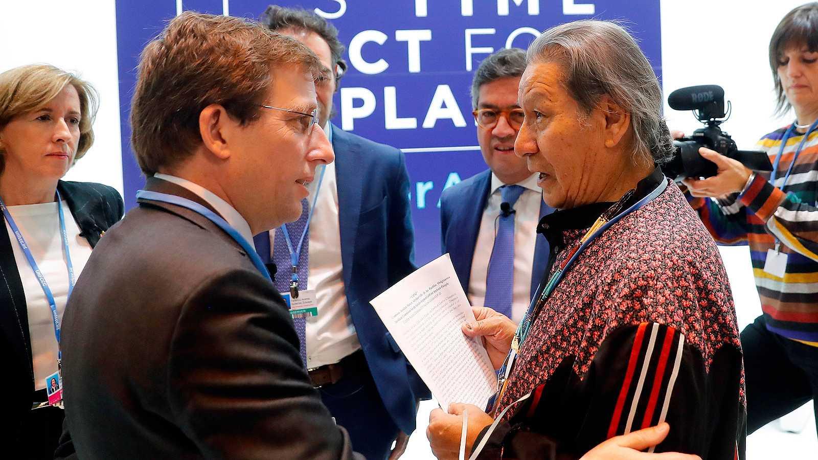 El alcalde de Madrid, JoséLuis Martínez-Almeida, conversa con el representante indígena que le ha reprochado que eligiera Notre Dame antes que el Amazonas