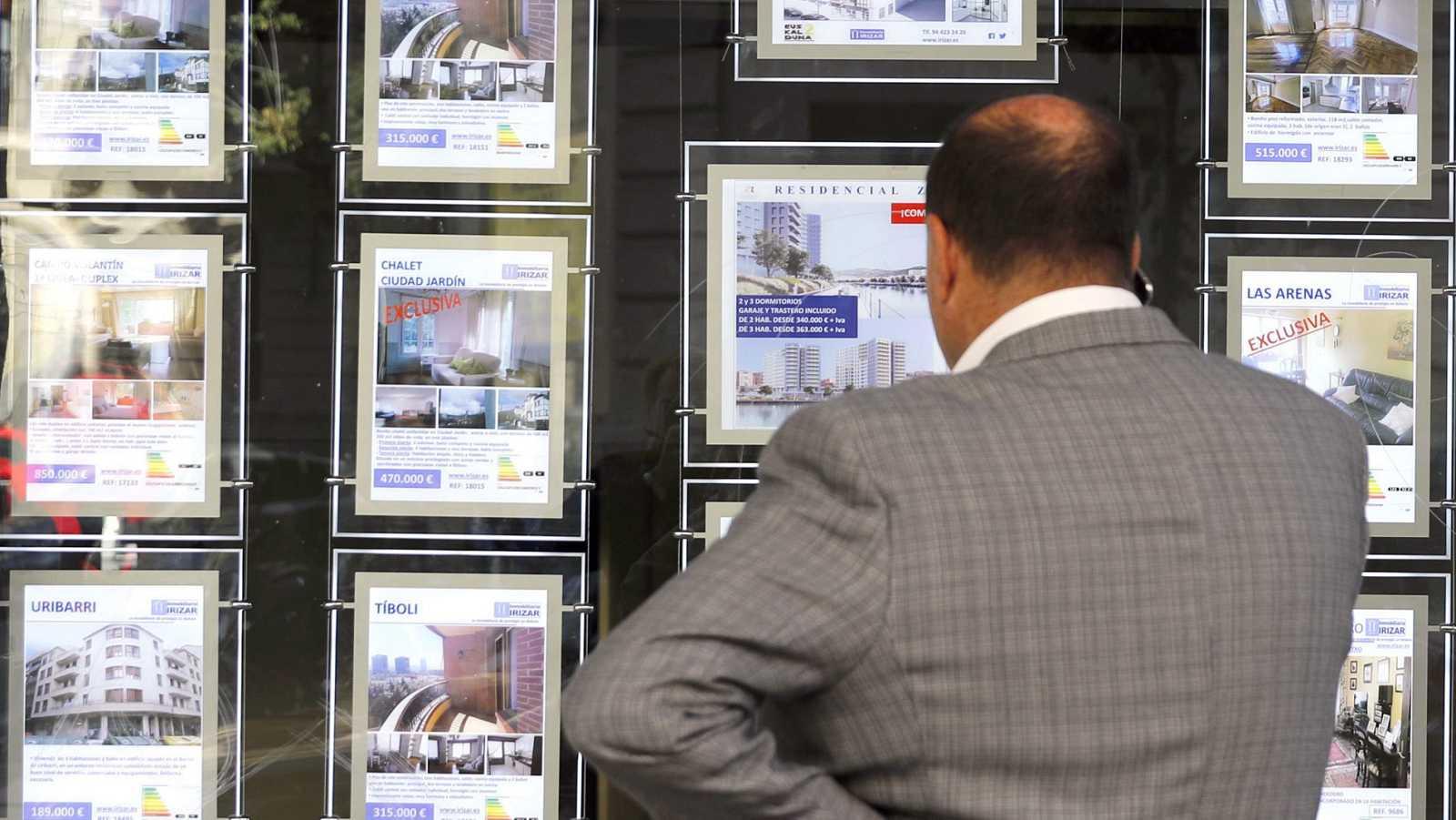 Una persona observa un escaparate de una inmobiliaria en Bilbao.