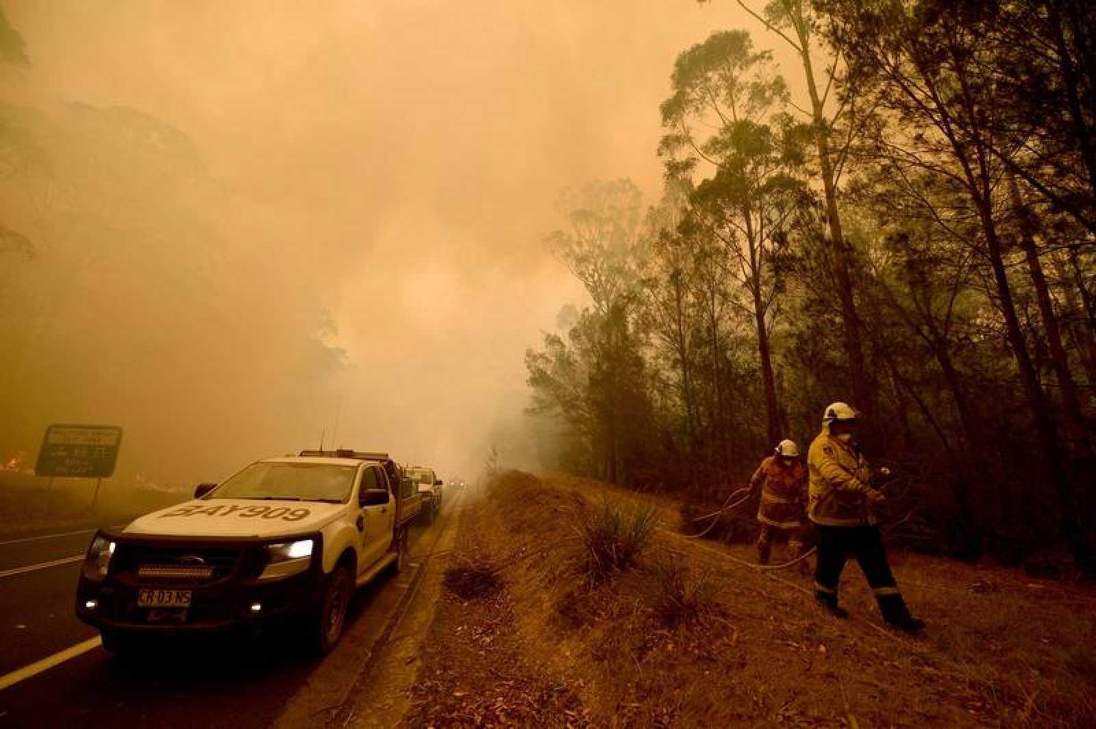 Los bomberos trabajan en las tareas de extinción de un incendio en la ciudad de Moruya