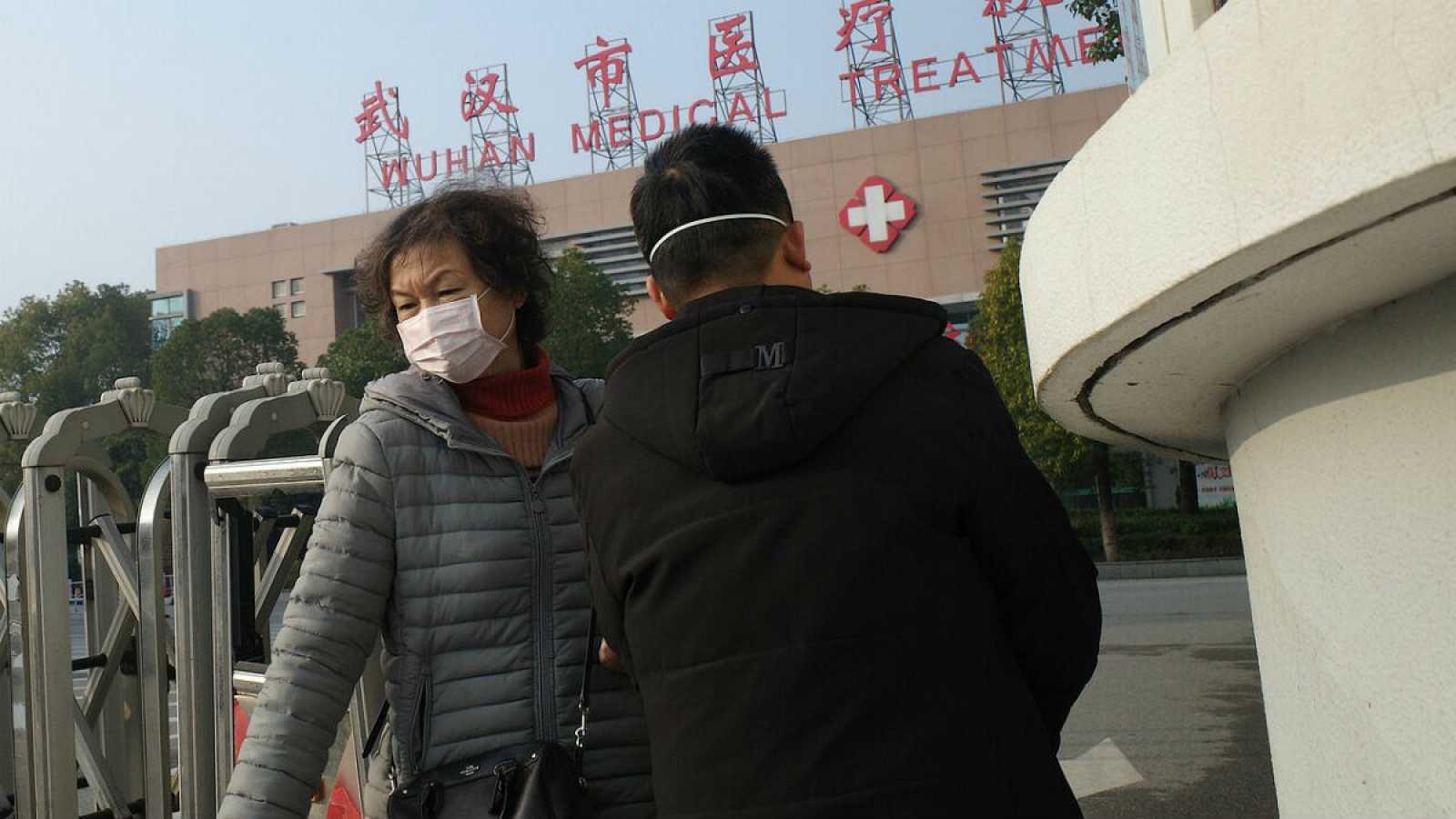 Una mujer abandona el centro médico de Wuhan, donde falleció un hombre que estaba ingresado por el coronavirus similar al síndrome agudo respiratorio grave (SARS).