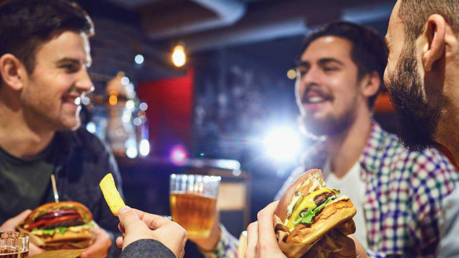 Un grupo de amigos come hamburguesas y bebe cerveza en un bar