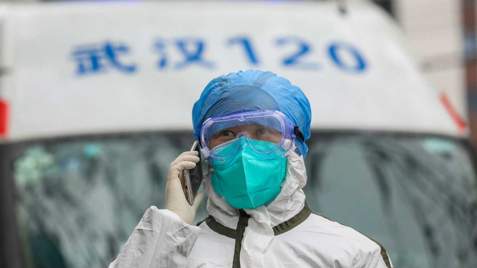 Una enfermera completamente protegida atiende una llamada junto a una ambulancia en Wuhan, origen del brote.