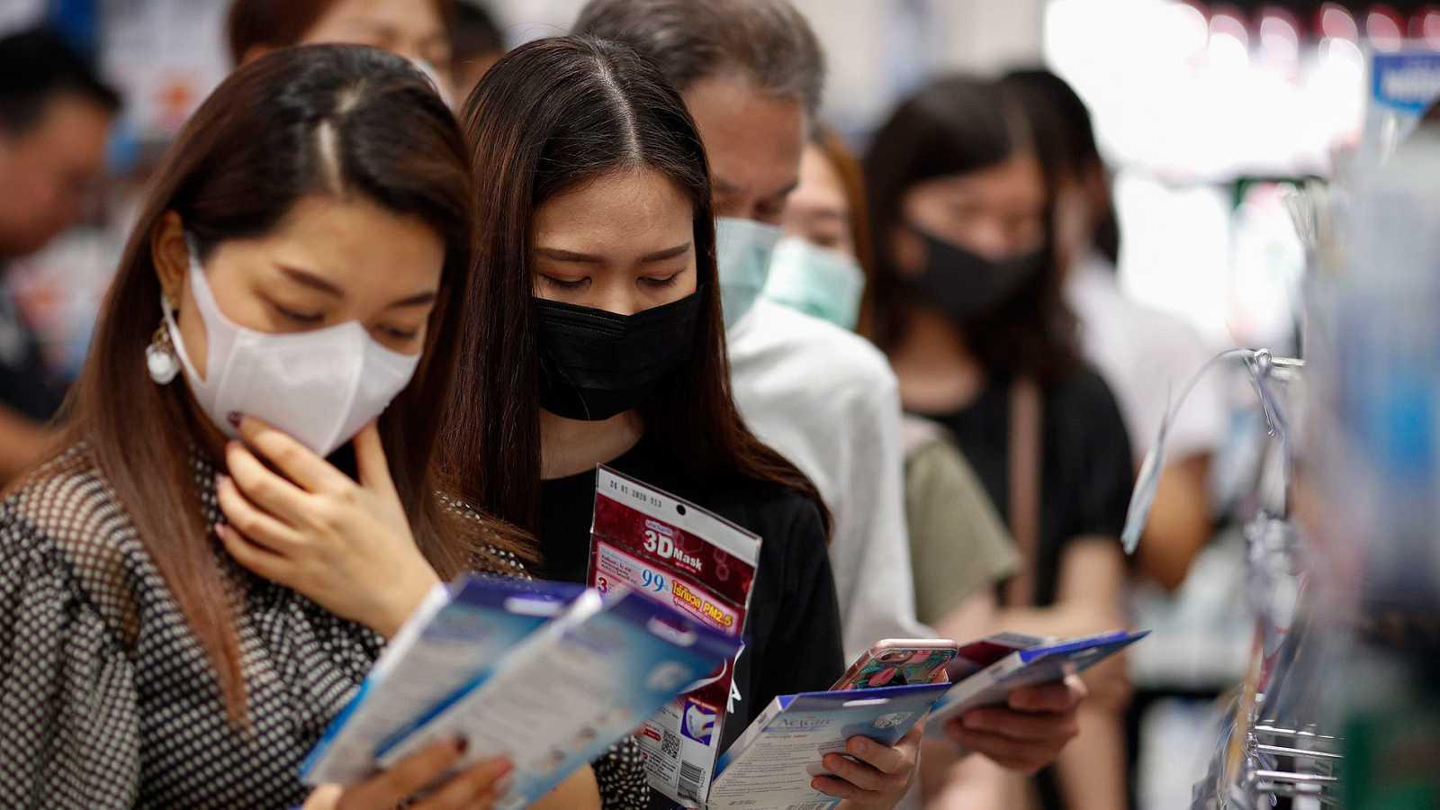 Un grupo de turistas chinos compra máscaras protectoras en un supermercado de Bangkok, Tailandia.