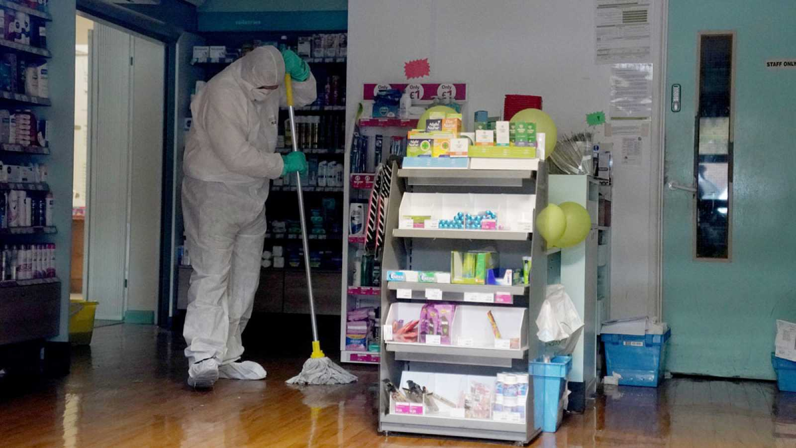 Un trabajador con traje protector limpia el centro médico, cerrado temporalmente en Brighton por coronavirus.