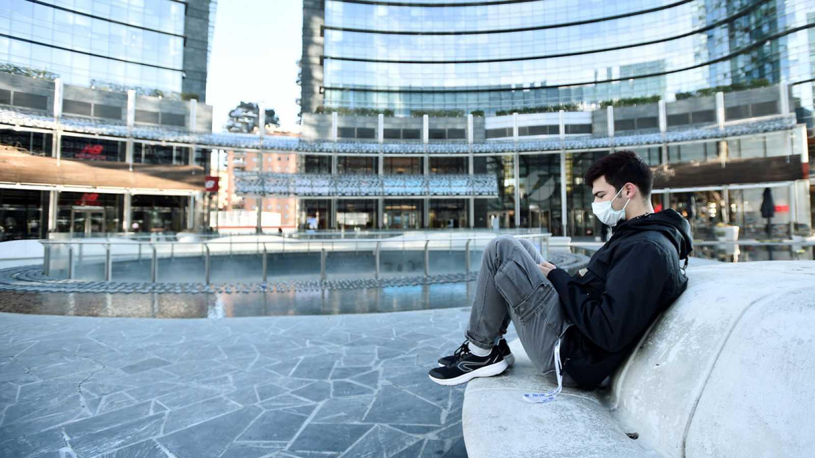 Un joven con mascarilla en Milán