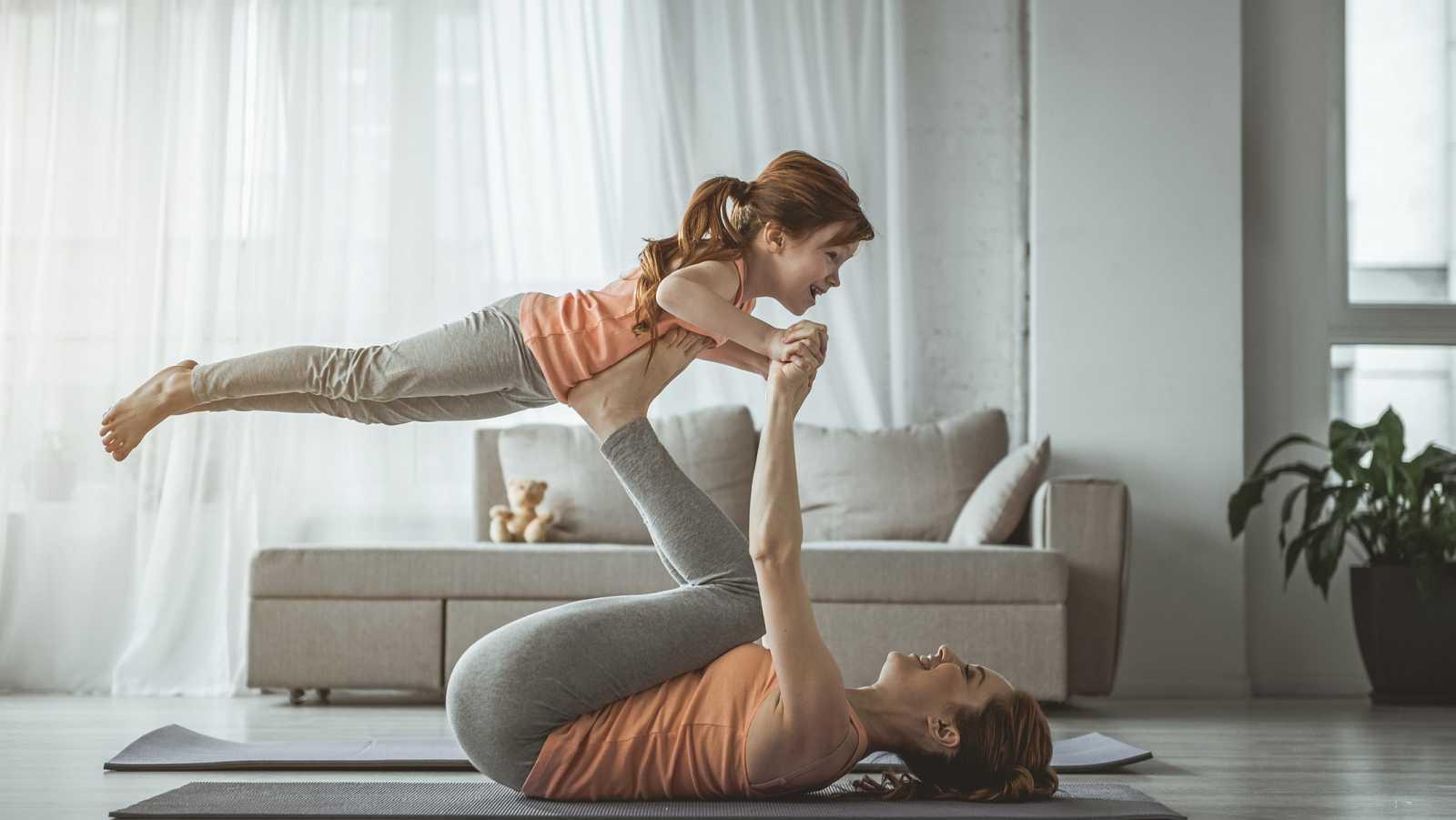 Una madre hace una rutina de gimnasia con su hija.