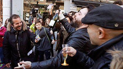 Varios vecinos brindan a las puertas de la administración situada en el Paseo de la Esperanza, número 4, en Madrid, donde se vendió el número 66.513, agraciado con el Gordo de Navidad en el año 2016