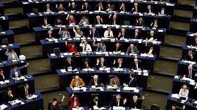 Varios diputados votan a mano alzada en el Parlamento Europeo