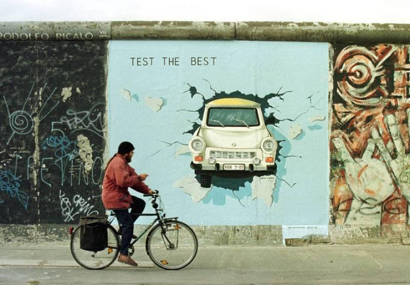 Un ciclista pasa ante una de las más famosas pintadas del Muro de Berlín, en la que un Trabant, un coche de la RDA, rompiendo el muro.