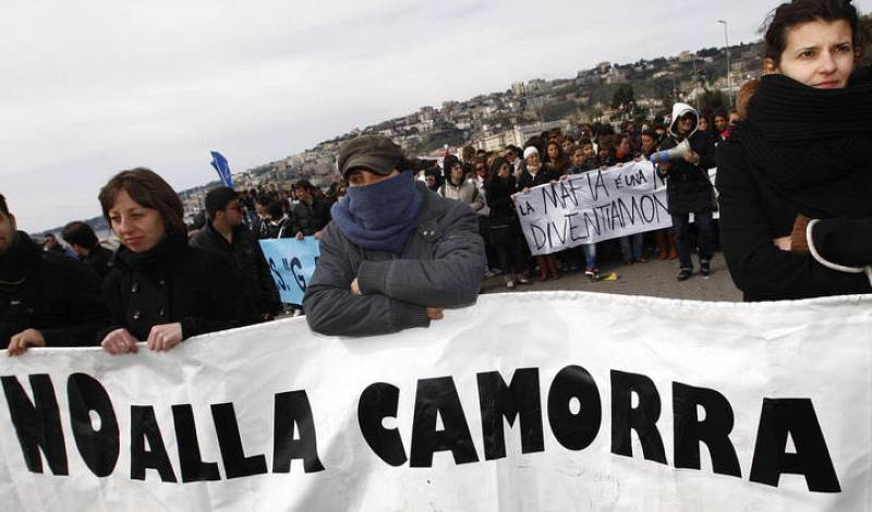 """Demonstrators hold a banner reading """"No to the Camorra"""" as they march in the southern city of Naples"""