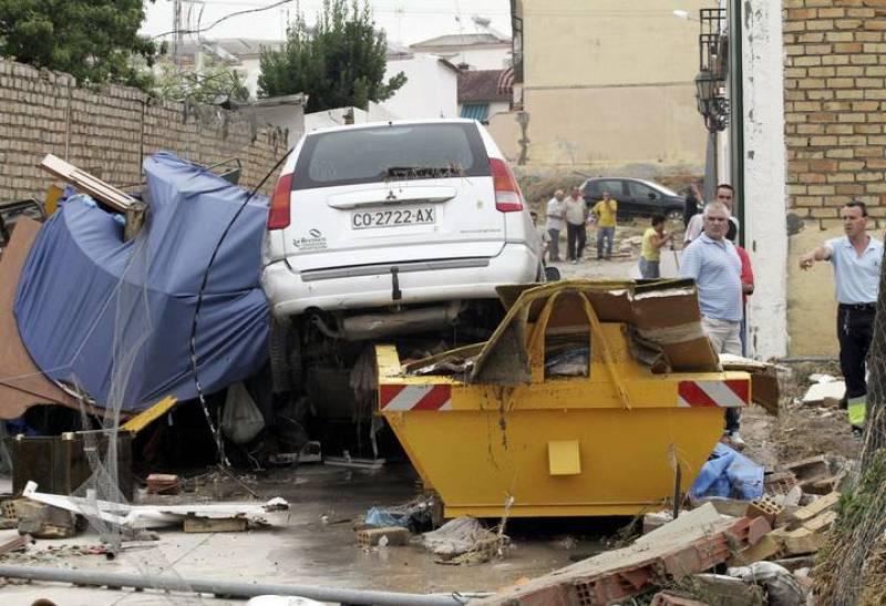Unos vecinos observan el estado en el que ha quedado una de las calles de la localidad de Aguilar de la Frontera después de las fuertes lluvias caídas en las últimas horas en la provincia de Córdoba que han provocado más de 200 incidencias y la muert