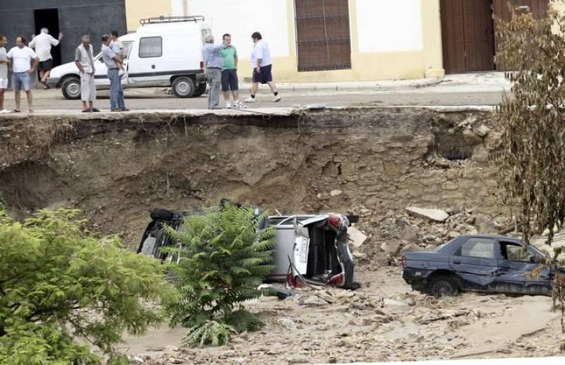 Vecinos de la localidad de Aguilar de la Frontera observan el estado en el que ha quedado varios coches.
