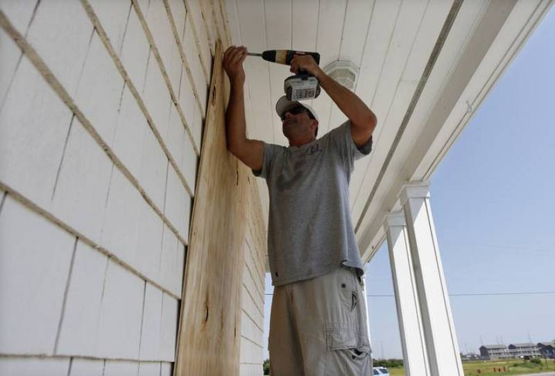 Worker boards up windows at a building during the approach of Hurricane Earl in Buxton on Cape Hatteras, North Carolina