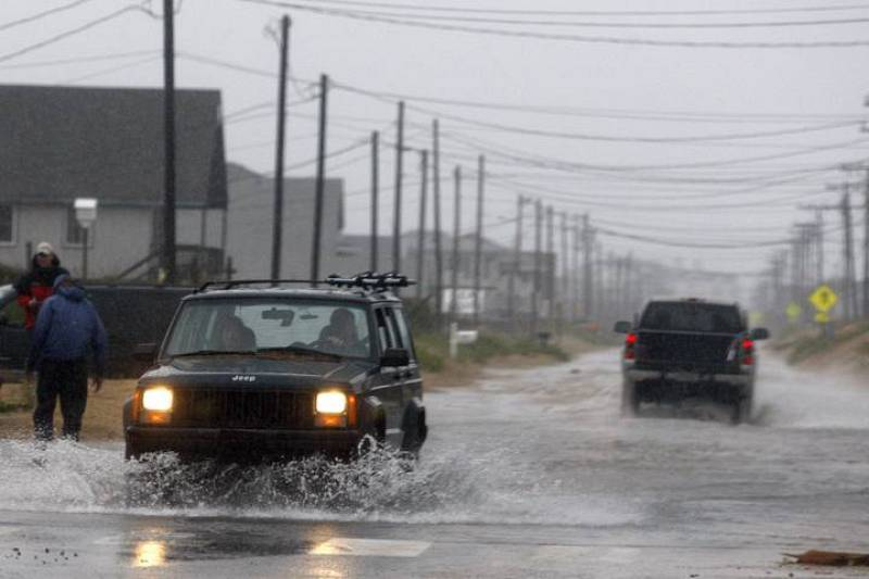 Cars pass along a flooded beach road during Hurricane Earl in Kill Devil Hills, North Carolina