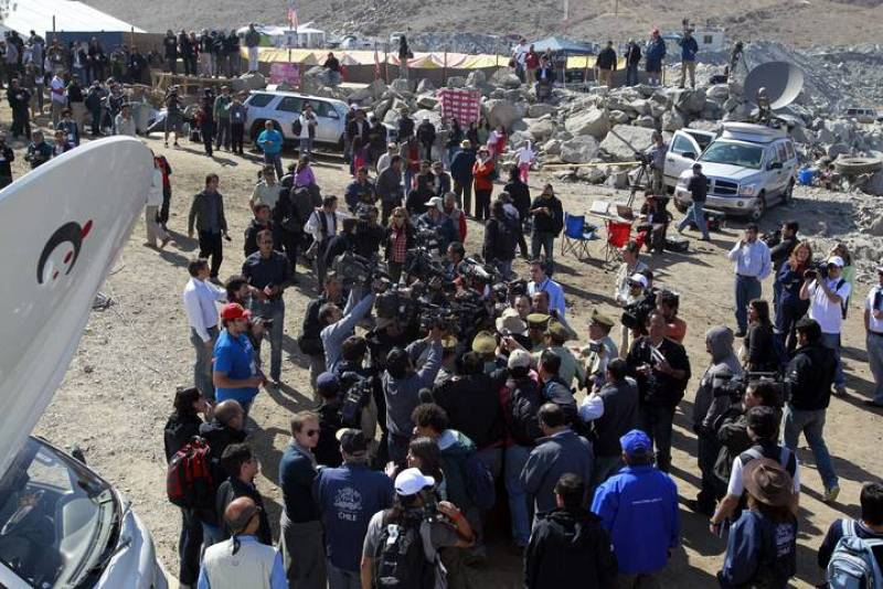 Members of the media gather as rescued Chilean miner Daniel Herrera arrives at the San Jose mine in Copiapo