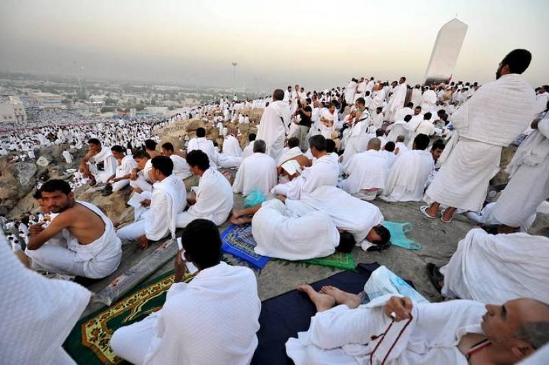 Peregrinos musulmanes realizan el rezo de alba antes de la salida del sol sobre Gebel Rahmah en el monte Arafat