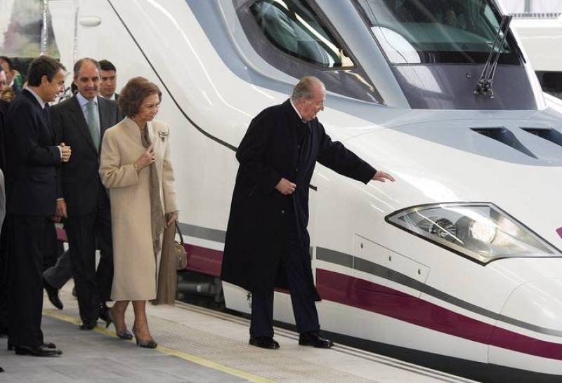 Spain's King Juan Carlos touches the AVE high speed train at the Joaquin Sorolla Station after it's inaugural journey in Valencia