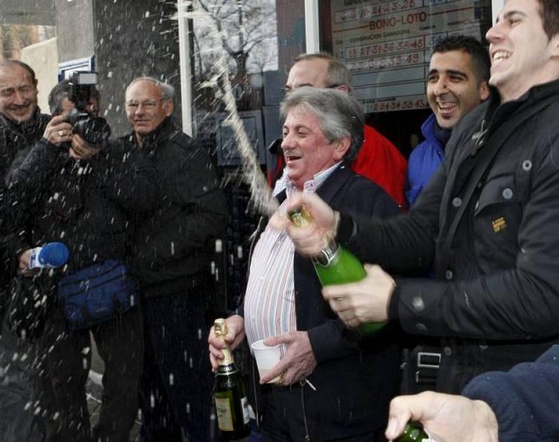 """José Luis Nieto (c), regente de la administración de loterías número 247 de Madrid, ubicada en el popular barrio de Ascao (Ciudad Lineal), donde se ha vendido íntegramente el número 70.013, primer premio del sorteo de la lotería de """"El Niño"""""""
