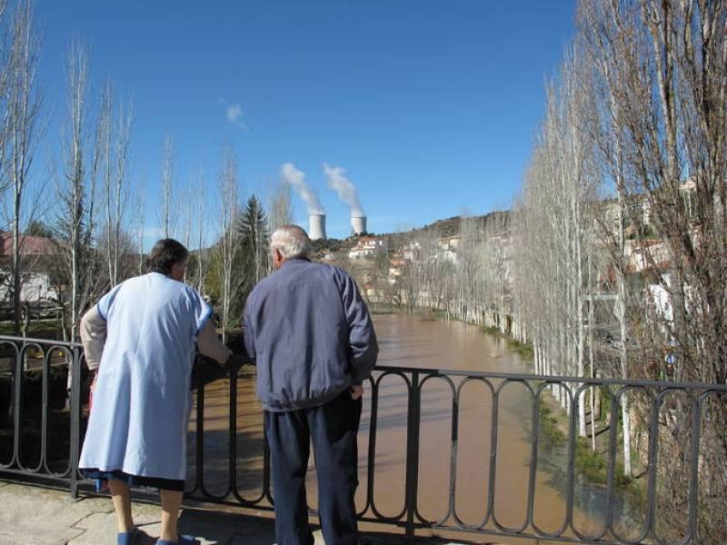 Dos vecinos de Trillo miran el cauce del río Tajo con las torres de la central nuclear al fondo.