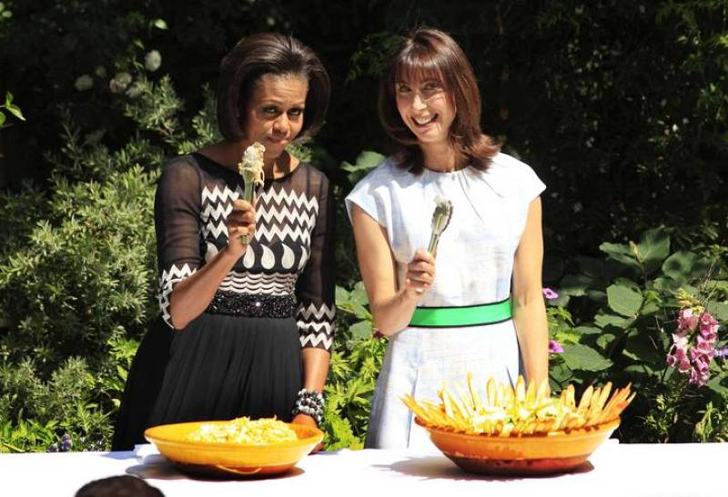 Michelle Obama (i) y Samantha Cameron (d) posan divertidas durante la barbacoa
