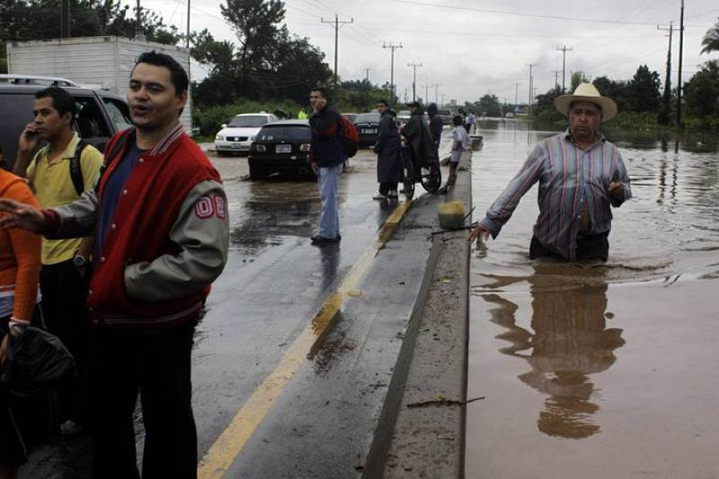 A man walks on a road that was flooded by the overflow of a river in the Ciudad Arce department of La Libertad