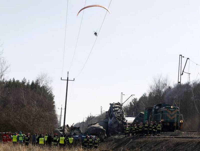 A para glider flies over the site of a train crash near the town of Szczekociny