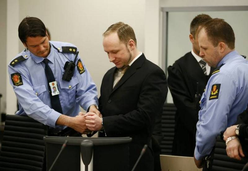 Defendant Norwegian mass killer Breivik has his handcuffs removed after arriving in the courtroom in Oslo