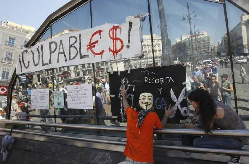 Un manifestante cuelga una pancarta en Sol