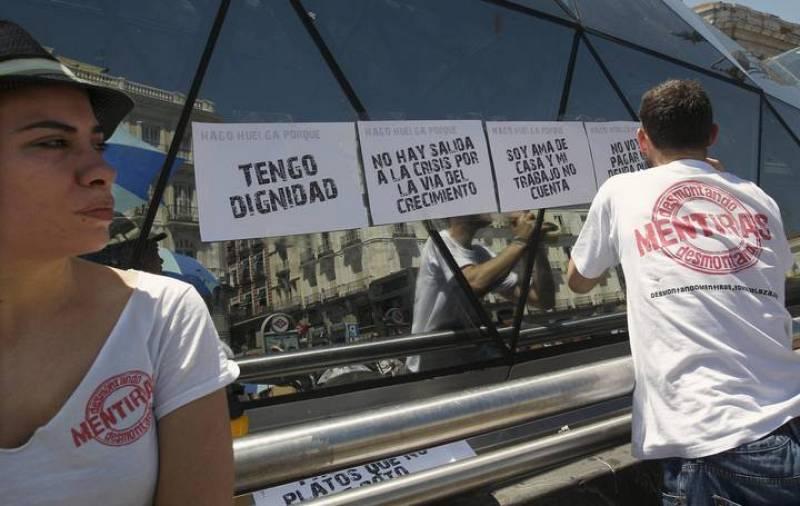 """Un """"indignado"""" pega varios carteles en la Puerta de Sol."""