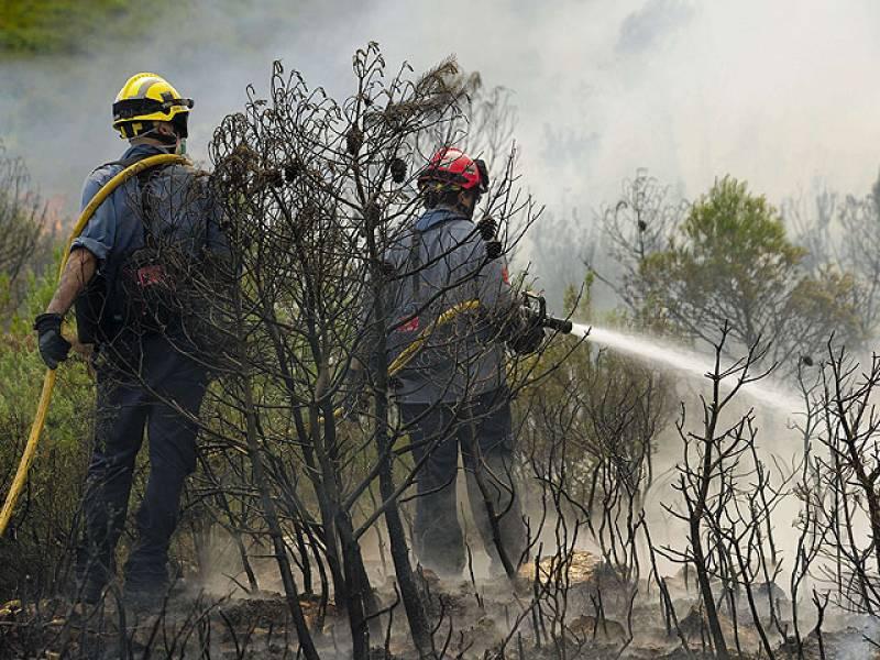 Dos bomberos mojan la zona en Rasquera este miércoles