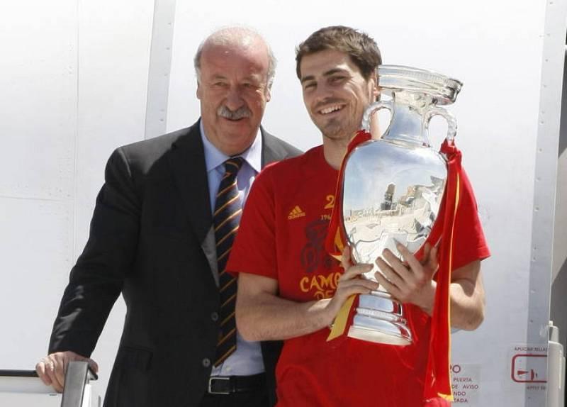 El capitán Íker Casillas posa con el trofeo de la Eurocopa, junto a Vicente del Bosque, en las escalerillas del avión.