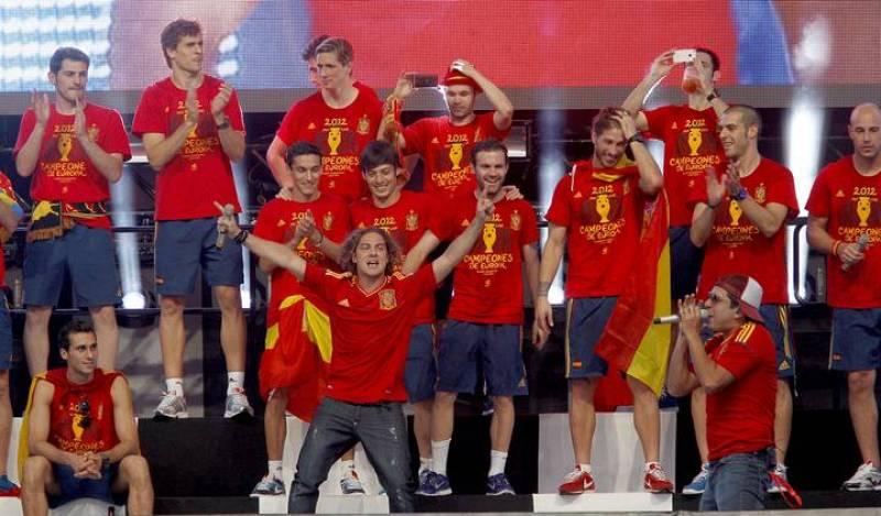 El cantante David Bisbal (c, primera fila) interpreta una canción junto a los jugadores de la selección española