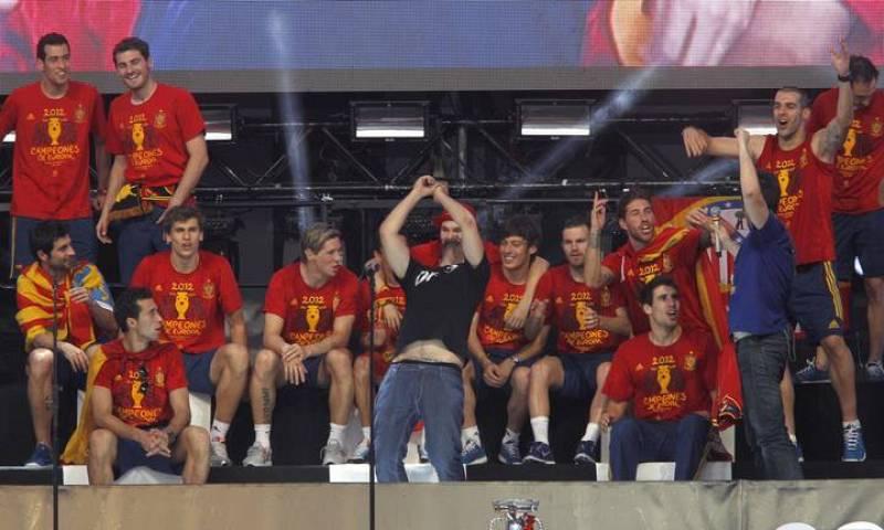 Los miembros del grupo Estopa David (c) y José (3d) cantan junto a los jugadores de la selección española en el escenario