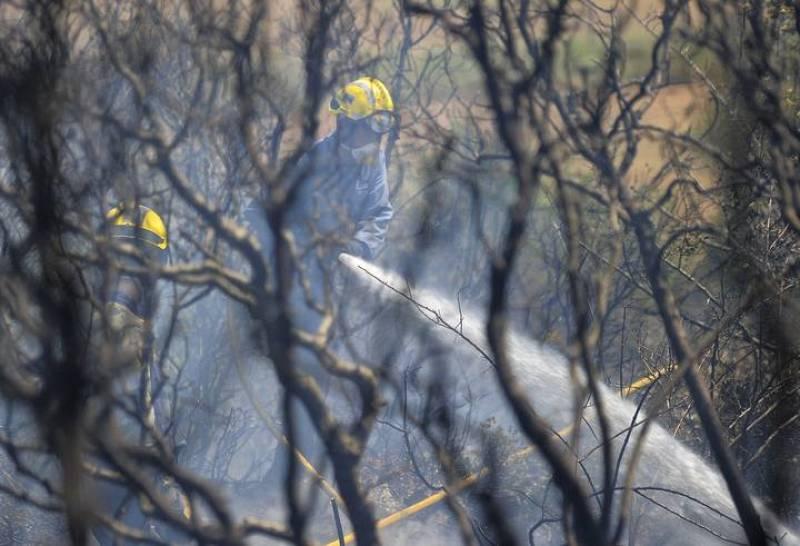 Un bombero trabaja para extinguir uno de los fuegos en el incendio de Girona.
