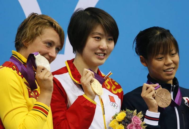 Las nadadoras Jiao Liuyang de China (c), oro, Mireia Belmonte García de España (i), plata, y Natsumi Hoshi de Japón (d), bronce, celebran en el podio de la prueba de los 200 metros mariposa.