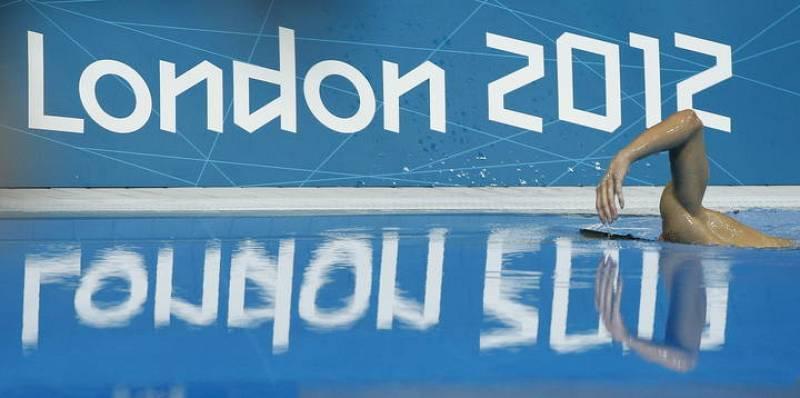 Michael Phelps, medalla de oro, se lanza a la piscina tras la prueba de 200 metros estilos.