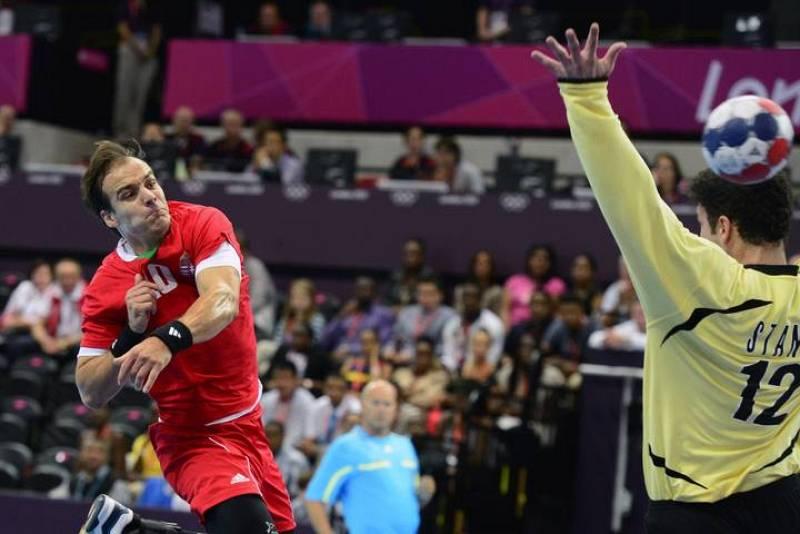 El jugador húngaro Gergely Harsanyi (L) dispara con la derecha para anotar frente al portero serbio Stanic Darko (R) durante el partido de balonmano Hungría vs Serbia en la ronda preliminar del grupo B.