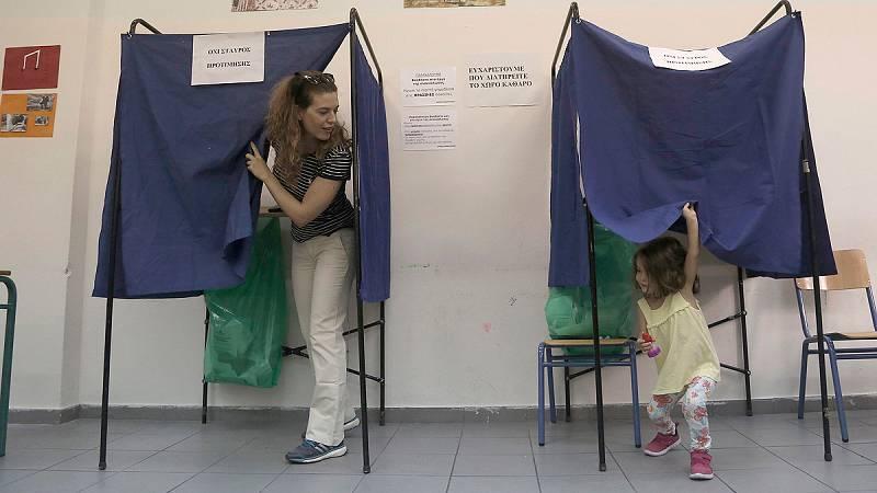Una mujer acude a votar con su hija