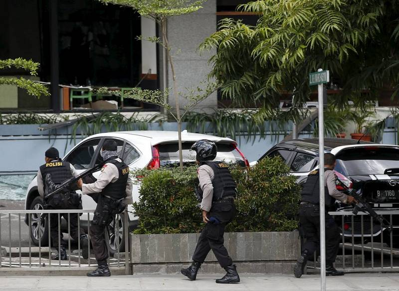 Agentes de la policía indonesia avanzan durante el tiroteo, mientras los asaltantes permanecen atrincherados
