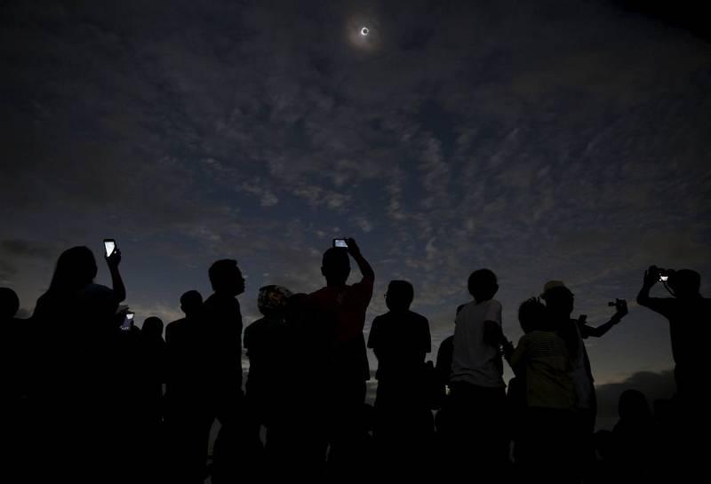 Un grupo de gente toma fotografías y observa el eclipse desde una playa de Ternate, en Indonesia.